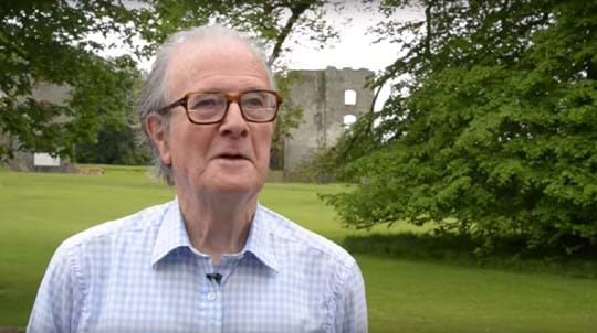 Grey haired man with glasses standing in landscaped grounds talks to camera