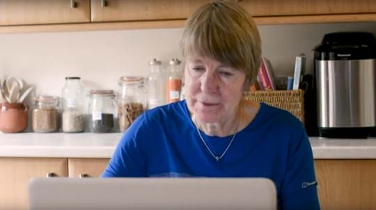 Volunteer Alison Stewart on a laptop in her kitchen