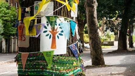 A roadside tree trunk decorated with bunting and pictures