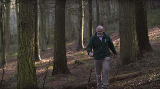 Site manager Mark Feather walking through woods