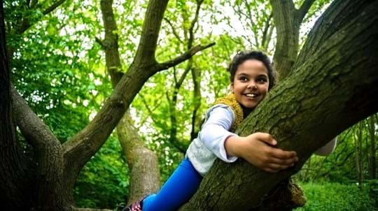 Smiling girl climbing a tree