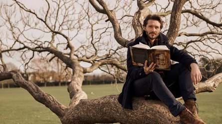 David Oakes sitting in an old gnarly tree holding a book
