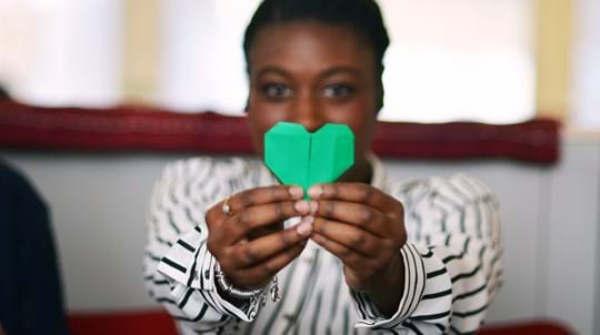 Close up of lady's hands holding a green paper heart
