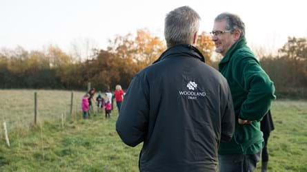 Man in Woodland Trust jacket giving advice to another man