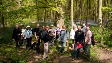 A group of people posing for a photo in a sunny wood before a walk