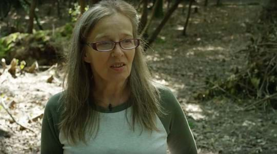 Woman with long hair and glasses in woodland talking to camera
