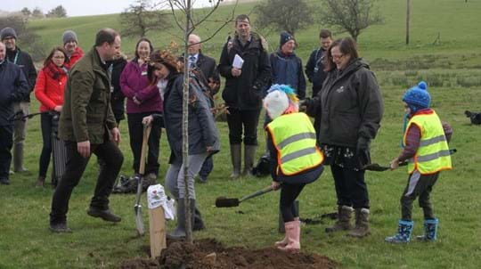Minister in coat and wellies planting a tree with two schoolchildren and onlookers in the background