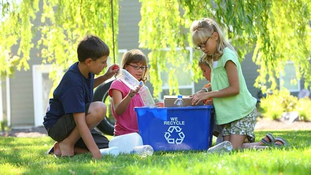 Three children recycling in garden