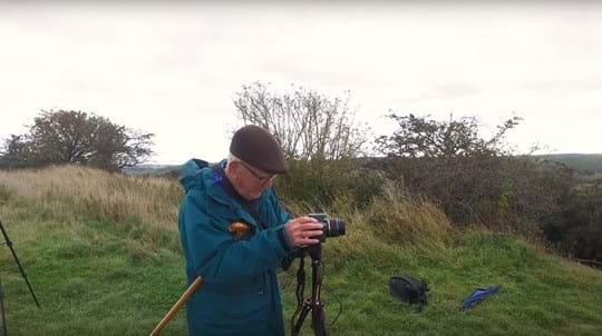 Volunteer David Rodway setting up a camera and tripod in a wood