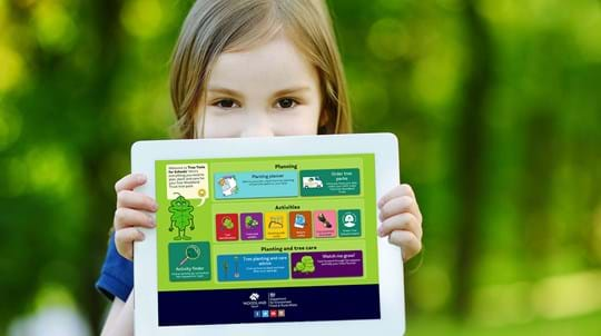 Child holding a tablet showing Tree Tools for Schools on it