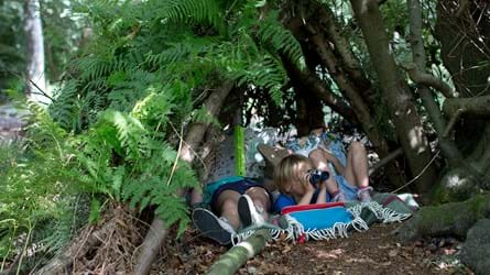 Two girls and a boy in a den. The girls have books and the boy has binoculars.