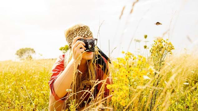 young woman photographing with camera in field