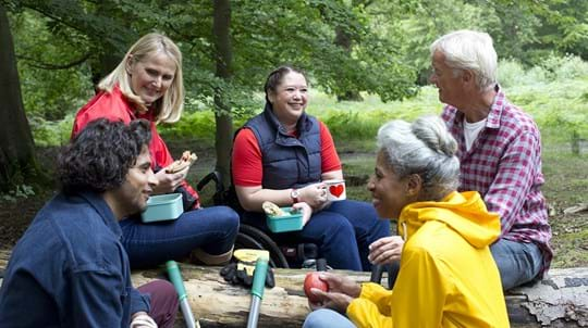 Group of five volunteers sitting in wood eating lunch and smiling