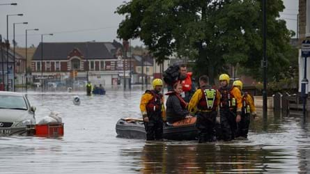 Rescuers in safety wear take a resident on a boat down a flooded street