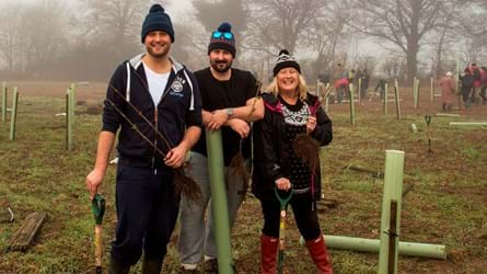 Two men and a woman in woolly hats and wellies rest against spades and tree guards at a planting event