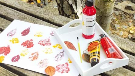 Leaf printing on paper with paint and supplies on a tray