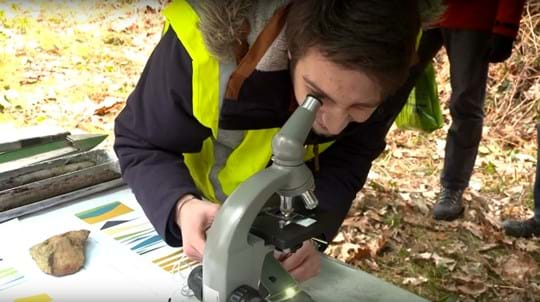 Visitor in hi-vis jacket looks at soil through a microscope