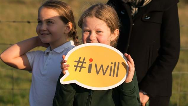 Girl holding #iwill campaign placard