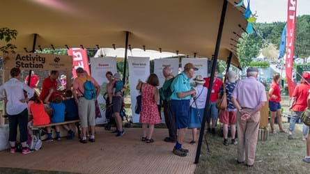 Several people look at various areas of a Woodland Trust festival stand on a sunny day