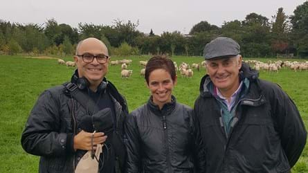 Adam, Helen and David wearing waterproofs stand in a field with sheep and trees in the background