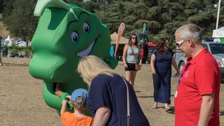 Person in leaf character costume shaking hands with a young child