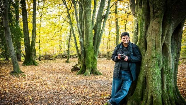 Volunteer photographer leans against a tree trunk while holding his camera