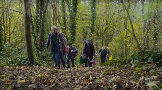 Group of volunteers walking through a wood with bags and tools