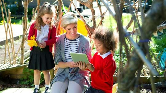 Teacher and pupils in an outdoor learning area with a tablet