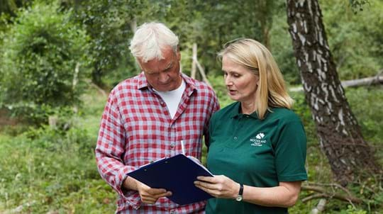 Volunteer explaining information to member of public in a wood setting