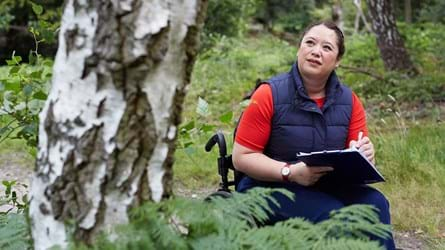 Lady looking at silver birch and noting information