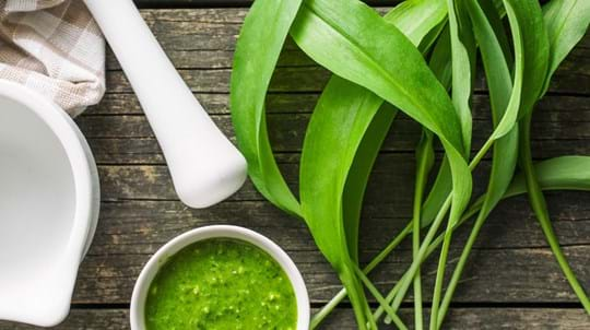Wild garlic pesto with pestle and fresh leaves